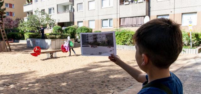 Junge auf einem Spielplatz betrachtet ein Foto
